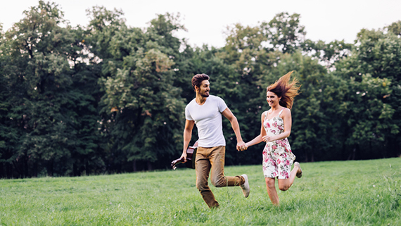 Couple Running through a field Living Life to the Fullest